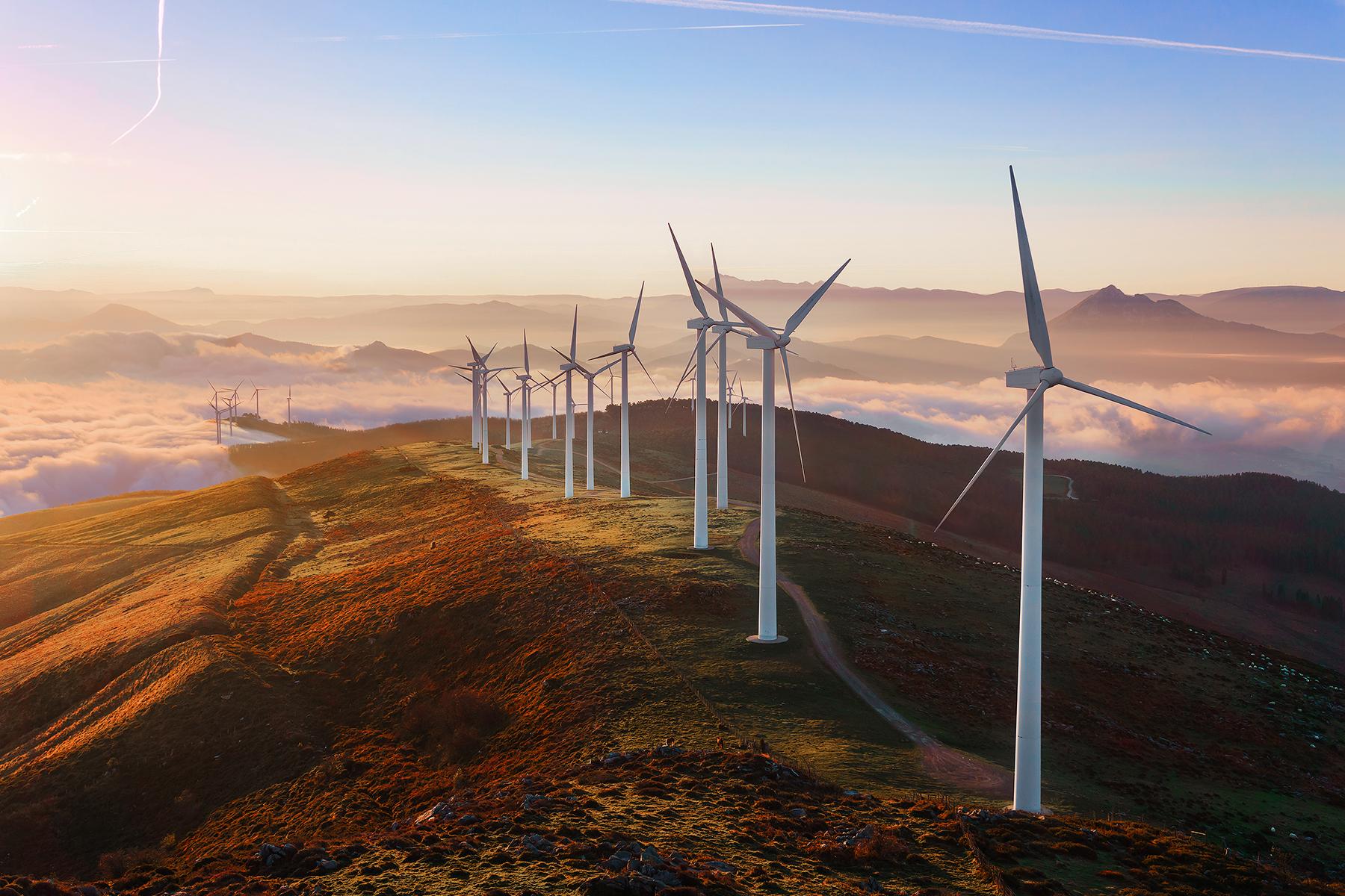 fotografia de cima de um morro com diversas turbinas de produção de energia eólica