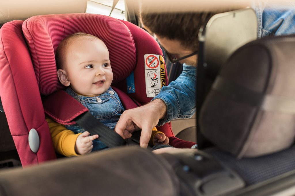 uma mulher colocando uma criança na cadeirinhas