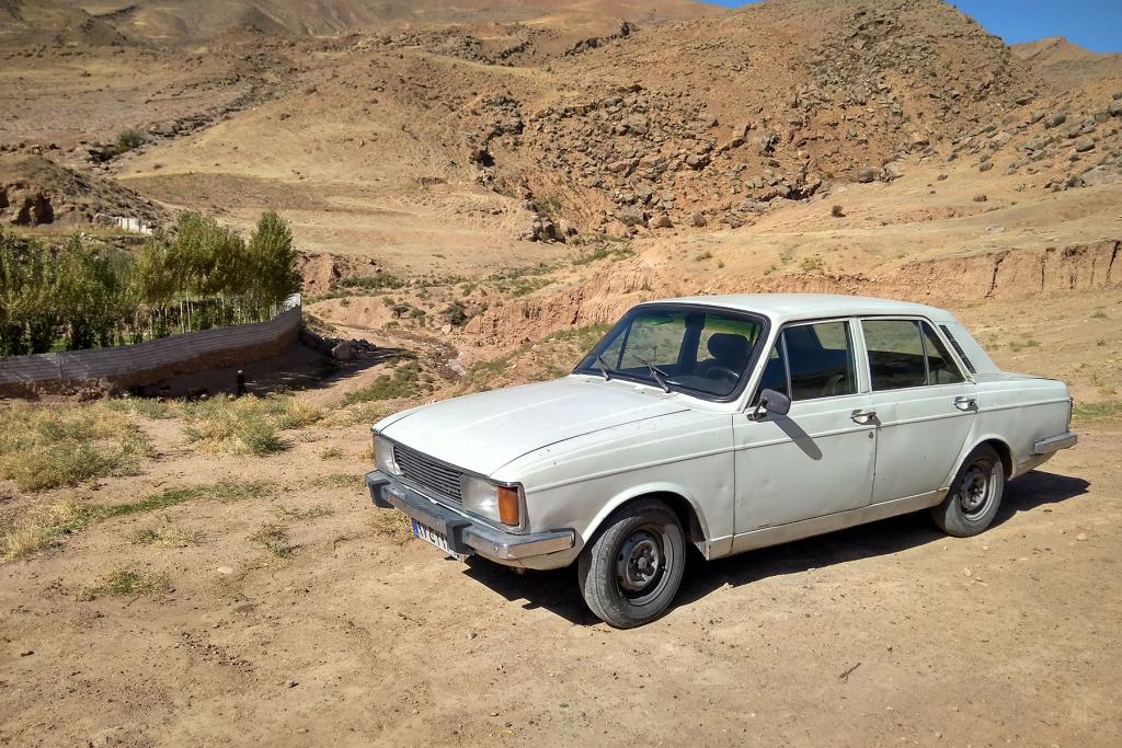 carro branco com nome de time de futebol no deserto.