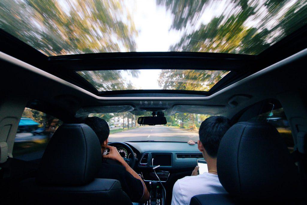 Carro com o teto solar aberto em uma estrada